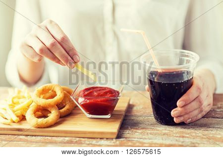 fast food, people and unhealthy eating concept - close up of woman with deep-fried squid rings, dipping french fries into ketchup bowl and drinking coca cola on wooden table poster