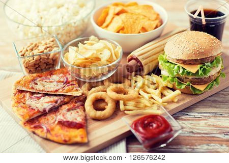 fast food and unhealthy eating concept - close up of fast food snacks and coca cola drink on wooden table poster
