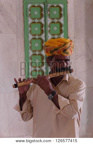 RAJASHAN, INDIA - MARCH 2016: A Rajasthani man with the colourful turban and large moustache, typical of that northwestern state of India, plays a traditional wooden flute with a traditional patterned, green window shutter in the background .