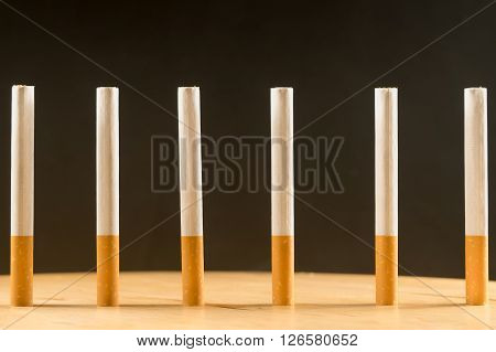 Six cigarettes standing in a row as a concept of prison bars.