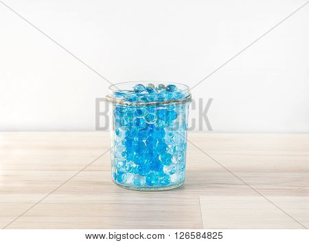 glass vase with hydrogel on wooden table with shadow