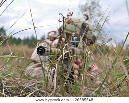 US Army soldier shooting his rifle while hiding in the grass