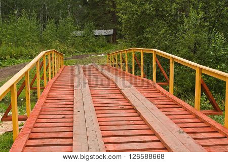 The new wooden bridge in the forest sunny summer day