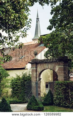 Green trees old gate red roofs and tower of church in Schwabach city Germany. City park.