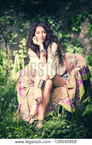 young barefoot woman in boho style clothes sit on armchair in garden full body shot summer day