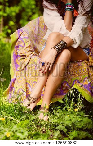 young barefoot  woman sit in garden on armchair wearing boho style clothes focus on hand with ring and massive bracelet, outdoor day shoot