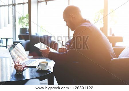Young man skilled CEO is checking time while is waiting with touch pad and net-book international partners. Male restaurant owner with portable digital tablet in hand is looking on his wrist watch