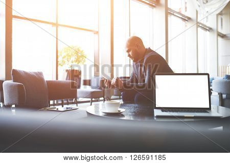 Man proud CEO is ordering o-nline via cell telephone car for business trip while is sitting in co-working cafe near table with open laptop computer with empty copy space screen for your advertising