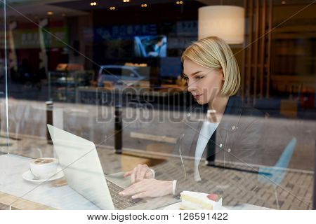 Young woman freelancer is ordering fly tickets on-line via laptop computer while is sitting in modern hipster coffee shop interior. Smart female remote programmer is using net-book for distance work