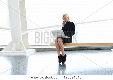 Confident woman skilled managing director having mobile phone conversation with her secretary while is sitting in modern office interior with open laptop computer during business travel in Hong Kong