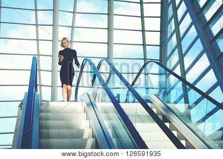 Businesswoman is reading financial news on web page via cell telephone while is going to work break on moving staircase of big skyscraper office. Woman is reading message on phone and use escalator