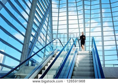 Female skilled CEO is dialing a number on mobile phone while is standing near escalator in interior with contemporary design. Woman is using cell telephone while is moving on staircase in office