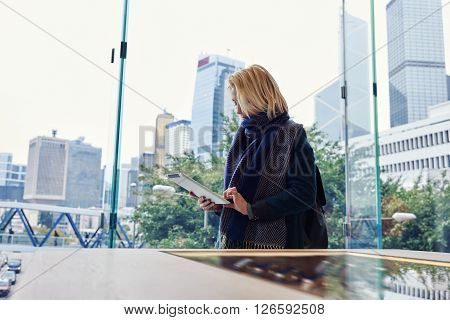 Hipster girl is browsing wireless on touch pad while is standing in modern interior with view of skyscrapers behind a window.Young woman is booking hotel via digital tablet during her business travel
