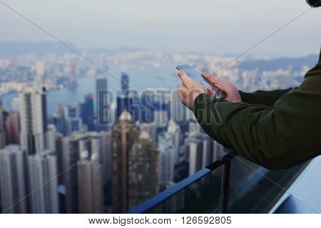 Close up business man is reading financial news in internet via cell telephone while is standing on skyscraper building roof with view of developed China's business center background with copy space