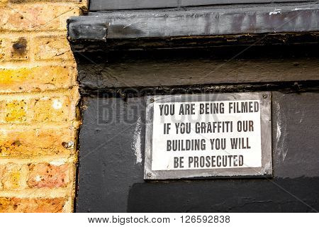 London United Kingdom - April 17 2016: Graffiti warning sign saying that you will be filmed and prosecuted if you do graffiti on this building (Rivingtn Street East London Shoreditch)