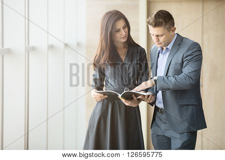 Business portrait of a girl and a guy in the interior of a modern business center with panoramic windows. Both are dressed in strict sofisnye costumes. Boss with interest the fact that he shows his employee with a magazine.