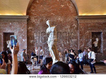 Paris France - May 13 2015: Tourists visit The Venus de Milo statue at the Louvre Museum in Paris. The Venus de Milo statue it's one of most important statue of the world.
