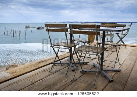 Table set up of a French bistro on a wooden terrace near Bordeaux