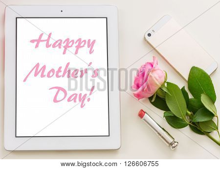 Styled desktop scene  with white tablet, mobile and flowers, happy mothers day greeting on screen