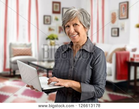 Senior woman using her handheld laptop as she stands in the living room of her house surfing the internet and looking at the camera with a smile