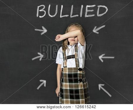 young sweet junior schoolgirl victim of bully crying sad standing in front of school class blackboard with chalk text bullied in school children bullying problem and education stress concept