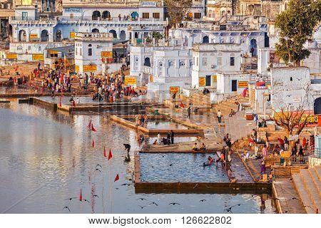 PUSHKAR, INDIA - NOVEMBER 20, 2012: Hindu devotees pilgrims bathing in sacred Puskhar lake (Sagar) on ghats of  Pushkar, Rajasthan. Pushkar is holy city for Hinduists and famous for many Hindu temples