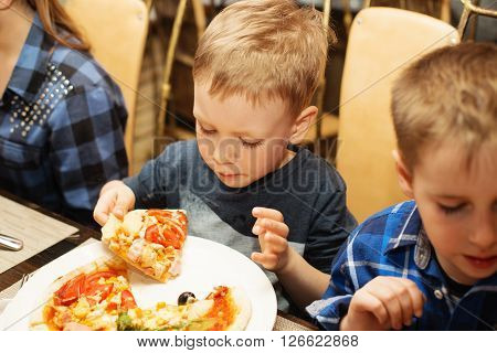 Children eat Italian pizza in the cafe. Adorable little boy eating pizza at a restaurant