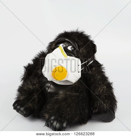 Black Toy Monkey In A Protective Mask On A White Background.