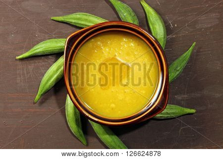 Overhead view of a bowl of Indian Arhar daal lentils and okra with a dollop of desi ghee or clarified butter.