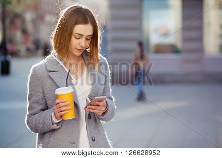 young beautiful happy stylish hipster girl with cocktail, smoozy drink and smartphone