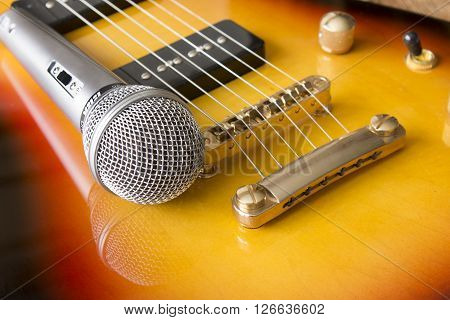 Electric guitar and microphone. Detail focus on microphone and strings. Shallow depth of field.