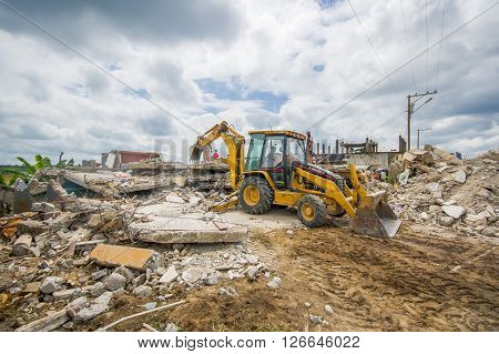 Portoviejo, Ecuador - April, 18, 2016: Rubble of a destroyed house after 7.8 earthquake, heavy machinery removes the debris