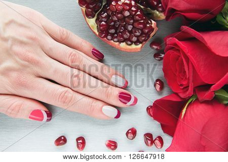 Skin care of a beauty female hand with grey pink and red asymmetry nail art manicure. And pockmarked grey background with red roses and sliced pomegranat