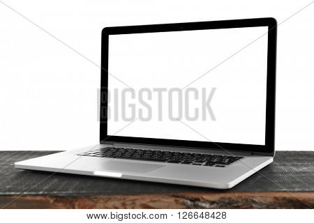 Laptop with black screen on wooden table against white background
