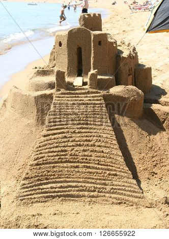 Sand Castle on nice beach with water at the ocean