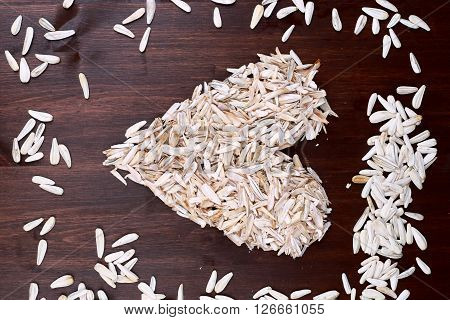 Sunflower seed in heart shaped on wood background