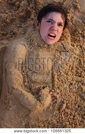preteen boy head in the beach sand happy smiling
