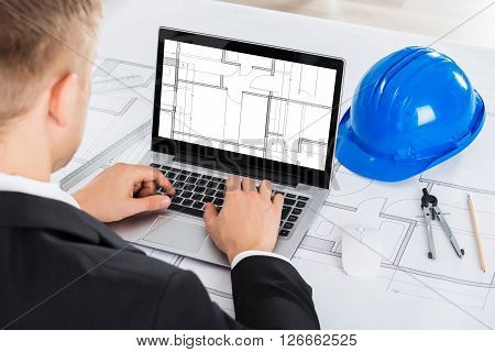 Male Architect Analyzing Blue Print On Computer Over Blue Print In Office