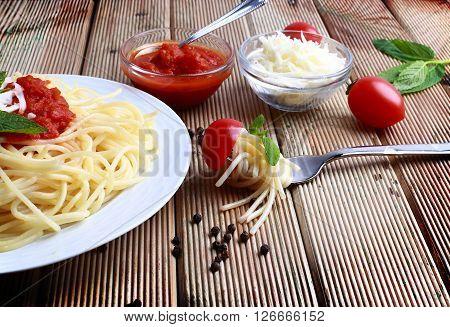 Spaghetti pasta with tomato sauce on wood background