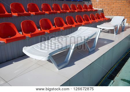 Chaise lounge for fire about tribunes of the swimming pool