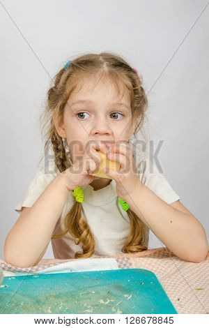 Six-year Girl With Pigtails Trying To Bite Off A Piece Of Cheese That Keeps Both Hands