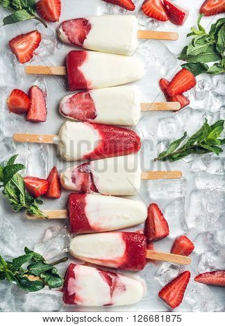 Strawberry yogurt ice cream popsicles with mint over steel tray background. Top view, vertical