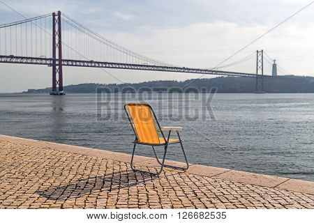 The yellow striped chair standing in front of the 25 de Abril Bridge that connects Lisbon Portugal with the municipality of Almada on the left bank of the Tejo river.
