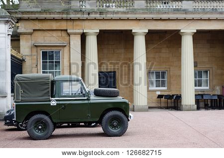 LONDON UK - APRIL 21 2016: Land Rover Defender in the grounds of Buckingham Palace. Old style green short wheel-base vehicle parked in the grounds of the London home of Queen Elizabeth II