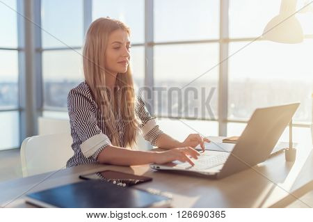 Young beautiful female copywriter typing texts and blogs in spacious light office, her workplace, using pc keyboard. Busy woman working