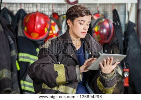 Firewoman Using Digital Tablet At Fire Station