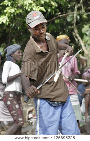 FOND BAPTISTE, HAITI - FEBRUARY 29, 2016:  Close-up of an unidentified man stripping a stalk of sugarcane with a long-bladed knife.  He's at the market in Fond Baptiste, Haiti.