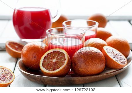 Fresh organic red oranges with delicious juice on white wooden table selective focus