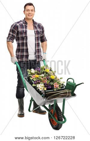 Full length portrait of a young guy posing with a wheelbarrow full of gardening equipment isolated on white background