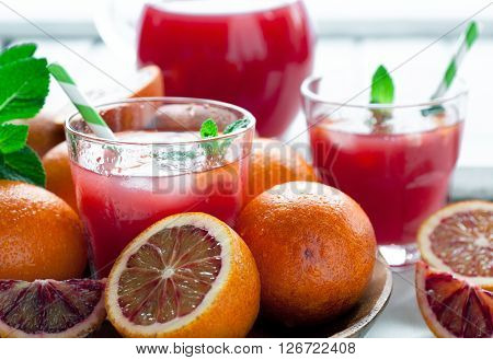 Delicious organic juice with red oranges on white wooden background selective focus toned